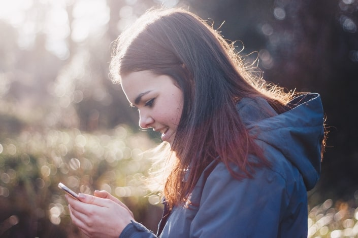 Woman smiling at a smart phone