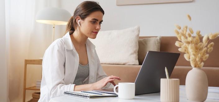 mujer en un headet trabajando con su computadora portátil