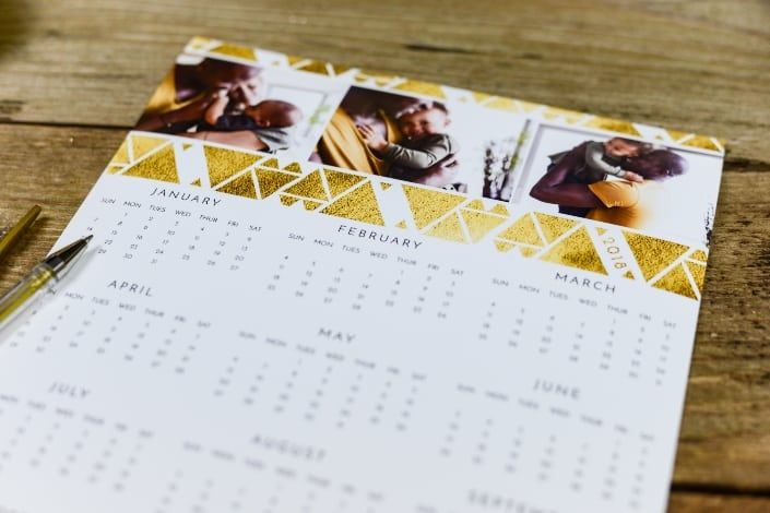 White and gold calendar on brown surface.