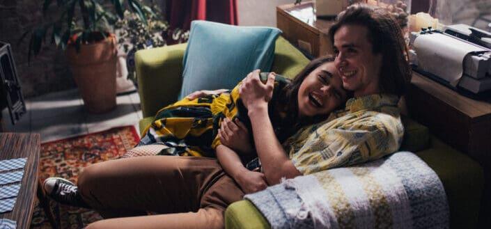 pareja riendo felizmente en el sofá