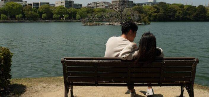 Pareja romántica sentada en un banco junto al lago