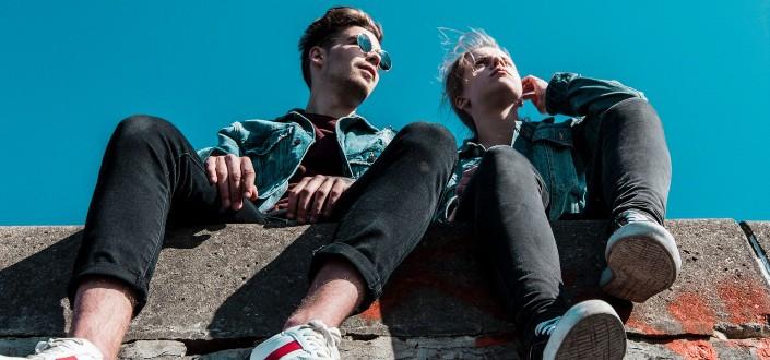 pareja sentada en el borde de un edificio bajo un cielo azul claro