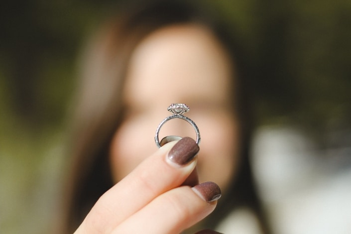 woman holding am engagement ring