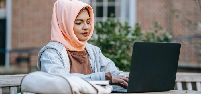 Elegante estudiante musulmana escribiendo en su computadora portátil