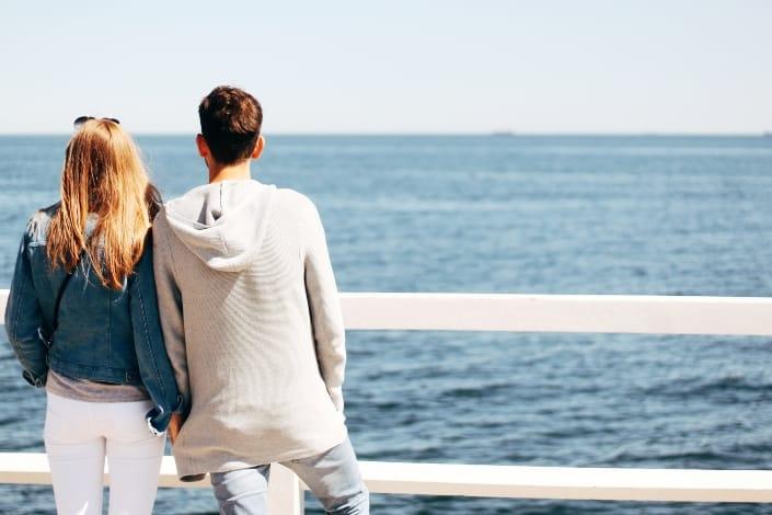 pareja junto a la barandilla de madera junto al cuerpo de agua