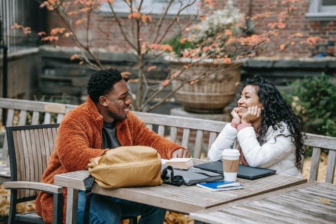 Alegres jóvenes estudiantes multiétnicas hablando y sonriendo - preguntas coquetas para hacerle a la persona que te gusta