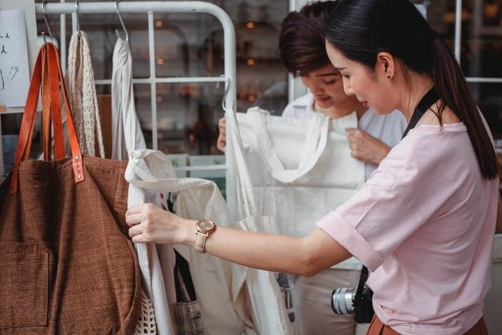 Mujeres asiáticas jóvenes de moda que eligen bolsas de algodón
