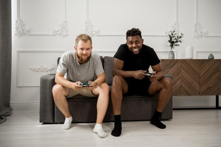 Dos amigos jugando videojuegos en casa
