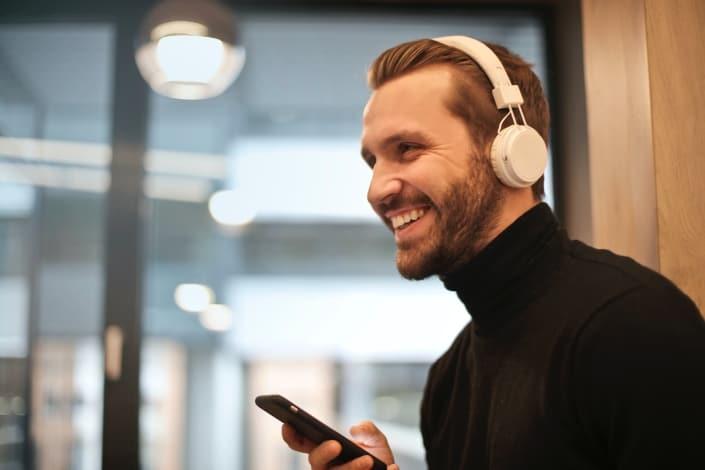Hombre vestido con auriculares blancos escuchando música